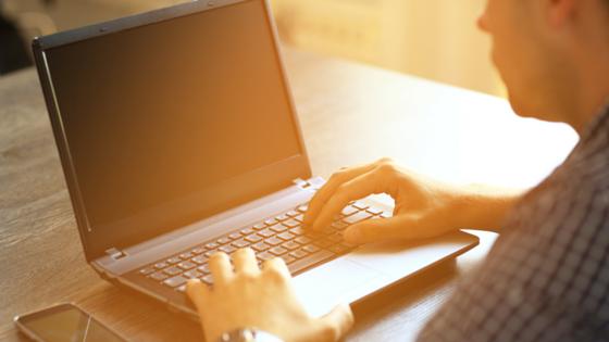 Man on his laptop in sunlight - Upstart Personal Loans