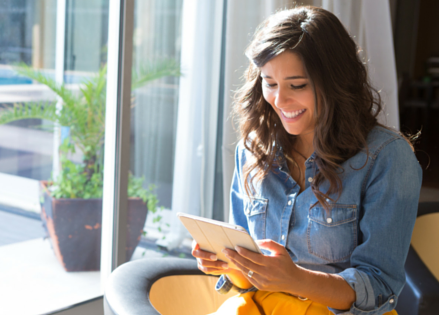 Woman using a tablet smiling - Upstart Personal Loans