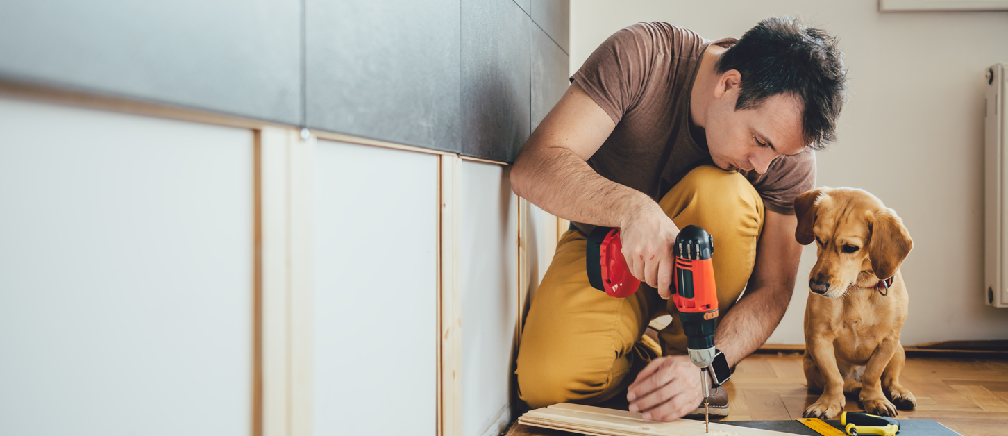 Man doing home improvements with his dog - Upstart Personal Loans