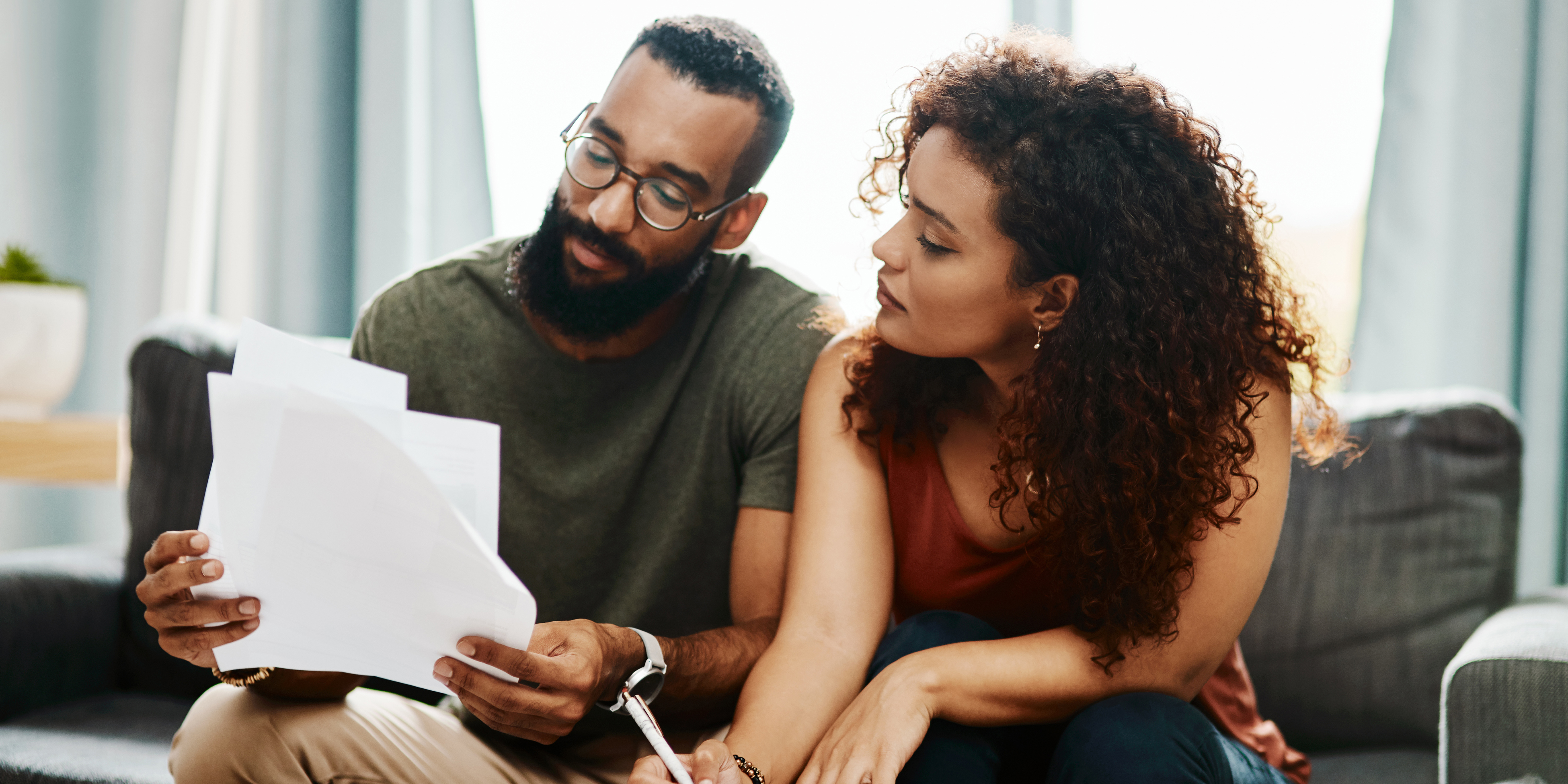 Couple looking at a tablet while sitting - Upstart Personal Loans