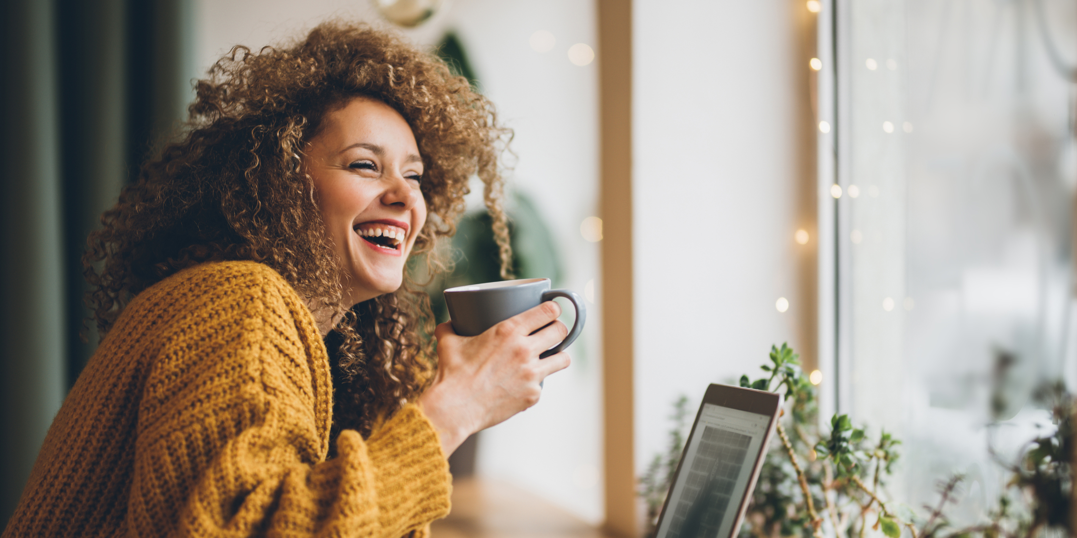 A woman laughing and having coffee - Upstart Personal Loans