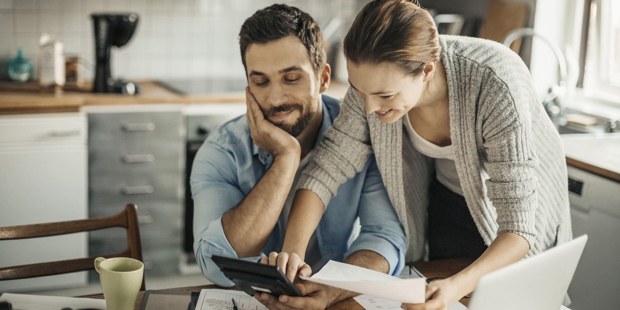 Couple looking at calculator - Upstart Personal Loans