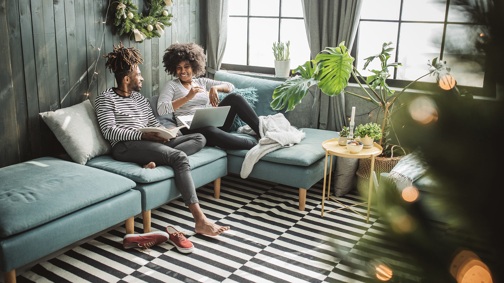 Two people sitting on a couch smiling - Upstart Personal Loans