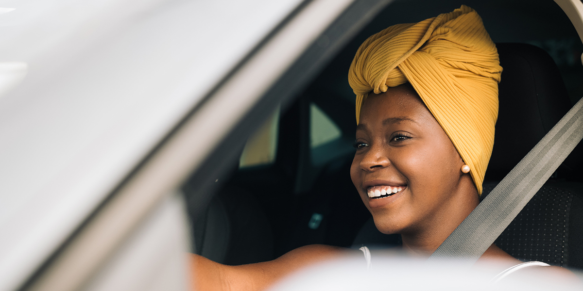 A woman driving in her car smiling - Upstart Personal Loans